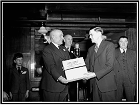 L'honorable Major-général L.R. LaFlèche, ministre des Services nationaux de guerre, reçoit des mains de F.R. Deakins, président de RCA Victor, des disques destinés aux prisonniers de guerre canadiens détenus dans les camps de détention allemands.