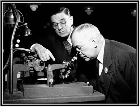 L'honorable Major-général L.R. LaFlèche, ministre des Services nationaux de guerre, examine un disque de phonographe sous les yeux de F.R. Deakins, président de RCA Victor.