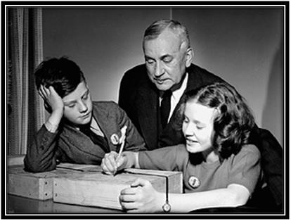 L'honorable Major-général L.R. LaFlèche, ministre des Services nationaux de guerre, regarde sa fille adresser un colis contenant des disques de phonographe sous les yeux de son fils lors d'une visite à l'usine R.C.A. Victor.